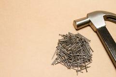 Martillo y pila de acero de clavos en fondo marrón Fotografía de archivo