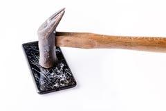 Martillo y smartphone con la pantalla quebrada en blanco foto de archivo
