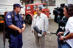 MARTIN BELL. SARAJEVO, BOSNIA, 19  APRIL 1996 - BBC chief war correspondent Martin Bell interviews a US volunteer firefighter in the Bosnian capital. Bell is now Royalty Free Stock Images