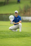 Martin Kaymer. On bended knee, Martin Kaymer, proudly shows his trophy, awarded to him, as the winner of the 2012 tournament Stock Image