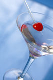 Martini. Vodka martini on blue background with red maraschino cherry on top royalty free stock image