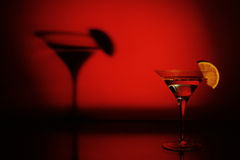 Martini. Shot of martini glass with sliced lemon with red spot light background showing its shadow Stock Photo