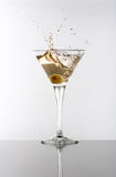 Martini. Olive splashing in a Martini glass Royalty Free Stock Images
