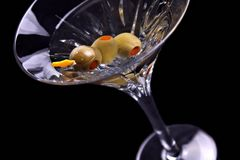 Martini on black with olives tilted Royalty Free Stock Photos
