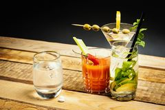 Martini and bloody mary drink and water and hangover pills. On a wooden table royalty free stock photo