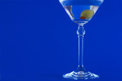 Martini on blue background. Martini with olive on blue background stock photography