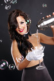 Martini and bubbles. Cute brunette serves a martini among bubbles Royalty Free Stock Photos
