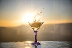 Martini cocktail glass in hand splashing on dark toned smoky background or colorful cocktail in glass with splashes and olives. Martini cocktail glass splashing stock images