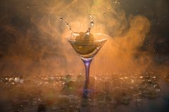Martini cocktail glass in hand splashing on dark toned smoky background or colorful cocktail in glass with splashes and olives. Martini cocktail glass splashing royalty free stock image