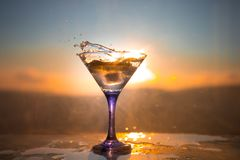 Martini cocktail glass in hand splashing on dark toned smoky background or colorful cocktail in glass with splashes and olives. royalty free stock photos
