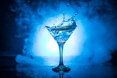 Martini cocktail glass in hand splashing on dark toned smoky background or colorful cocktail in glass with splashes and olives. Martini cocktail glass splashing stock photos