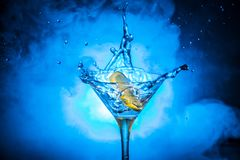 Martini cocktail glass in hand splashing on dark toned smoky background or colorful cocktail in glass with splashes and olives. Martini cocktail glass splashing royalty free stock photos