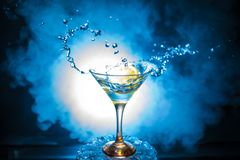 Martini cocktail glass in hand splashing on dark toned smoky background or colorful cocktail in glass with splashes and olives. Martini cocktail glass splashing royalty free stock images