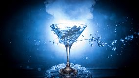 Martini cocktail glass in hand splashing on dark toned smoky background or colorful cocktail in glass with splashes and olives. Martini cocktail glass splashing royalty free stock photography