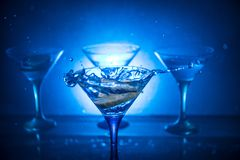 Martini cocktail glass in hand splashing on dark toned smoky background or colorful cocktail in glass with splashes and olives. Martini cocktail glass splashing royalty free stock photo