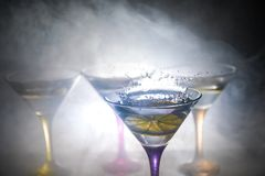 Martini cocktail glass in hand splashing on dark toned smoky background or colorful cocktail in glass with splashes and olives. Martini cocktail glass splashing stock photo