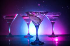 Martini cocktail glass in hand splashing on dark toned smoky background or colorful cocktail in glass with splashes and olives. Martini cocktail glass splashing stock image