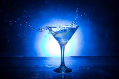 Martini cocktail glass in hand splashing on dark toned smoky background or colorful cocktail in glass with splashes and olives. royalty free stock photo