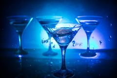 Martini cocktail glass in hand splashing on dark toned smoky background or colorful cocktail in glass with splashes and olives. Martini cocktail glass splashing stock photography