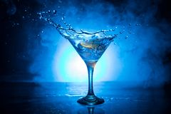 Martini cocktail glass in hand splashing on dark toned smoky background or colorful cocktail in glass with splashes and olives. stock image