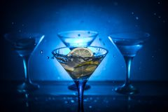 Martini cocktail glass in hand splashing on dark toned smoky background or colorful cocktail in glass with splashes and olives. stock photo