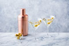Martini cocktail with green olives, shaker on marble table background. Martini cocktail with green olives, shaker on marble table background stock photos