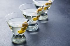 Martini cocktail with green olives. Slate background. Close up. Stock Images