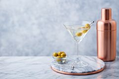Martini cocktail with olives and bar shaker on marble table background. Copy space. Martini cocktail with olives and bar shaker on marble table background. Copy royalty free stock image