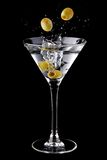 Martini cocktail with olives and splash. Isolated on a black background Royalty Free Stock Photos
