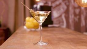 Martini coctailexponeringsglas med oliv i det på en stångräknare lager videofilmer