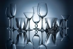 Martini, cognac, champagne and wine empty glasses with reflections. On grey royalty free stock image