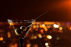 Martini con las aceitunas en un fondo de la ciudad de la noche Imagen de archivo libre de regalías