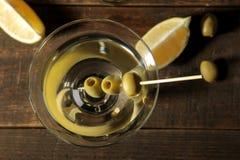 Martini em um copo de vinho de vidro com azeitonas verdes em um espeto em uma tabela de madeira marrom cocktails Barra foto de stock royalty free