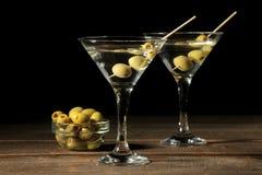 Martini em um copo de vinho de vidro com azeitonas verdes em um espeto em uma tabela de madeira marrom cocktails Barra fotografia de stock royalty free
