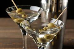 Martini em um copo de vinho de vidro com azeitonas verdes em um espeto em uma tabela de madeira marrom cocktails Barra imagens de stock