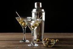 Martini em um copo de vinho de vidro com azeitonas verdes em um espeto em uma tabela de madeira marrom cocktails Barra fotografia de stock