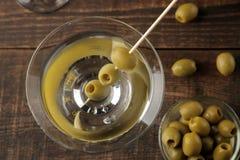 Martini em um copo de vinho de vidro com azeitonas verdes em um espeto em uma tabela de madeira marrom cocktails Barra fotos de stock royalty free