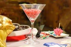 Martini exponeringsglas fyllde med rosa jellybeans på tabellen med spridda drinkparaplyer och mestadels den tomma valentinchoklad fotografering för bildbyråer