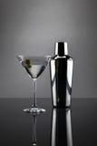 Martini exponeringsglas och shaker på grå bakgrund Royaltyfri Fotografi