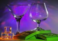 Martini exponeringsglas samman med konjakskupa på packar av 100sen av oss dollar och iskuber med att exponera på ljusa violetta royaltyfria foton