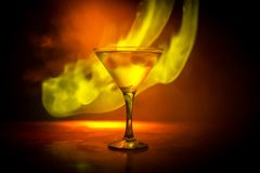 Martini in fire concept. Glass of famous cocktail Martini burning in fire at dark toned foggy background. Selective focus stock image