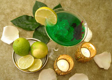 Martini-Glas mit Kalken auf einer Platte und Kerzen Stockfoto