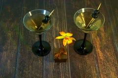 Martini-Glas mit Oliven mit Geschenkbox und gelber Orchidee auf einem Holztisch stockfoto