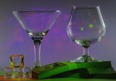 Martini-Glas samen met Cognacglas op pakken van 100s van ons dollars en ijsblokjes met opvlammende vlotte violette lichten  stock foto's
