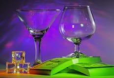 Martini-Glas zusammen mit Kognak-Glas auf Sätzen des 100s von US-Dollars und Eiswürfel mit blinkenden hellen violetten Lichtern stockfotografie