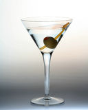 Martini glass. Swirl in Martini glass with olive and swizzle stick, yellow stirrer Royalty Free Stock Photo