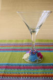Martini Glass and Cocktail Sticks. Martini Glass with beaded rings on a colorful placemat Royalty Free Stock Image