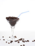 Martini glass with coffee beans and straw Royalty Free Stock Images