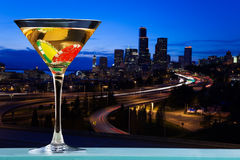 Martini glass with dibs against city skyline Royalty Free Stock Photos