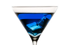Martini glass with ice and blue liqueur Royalty Free Stock Images